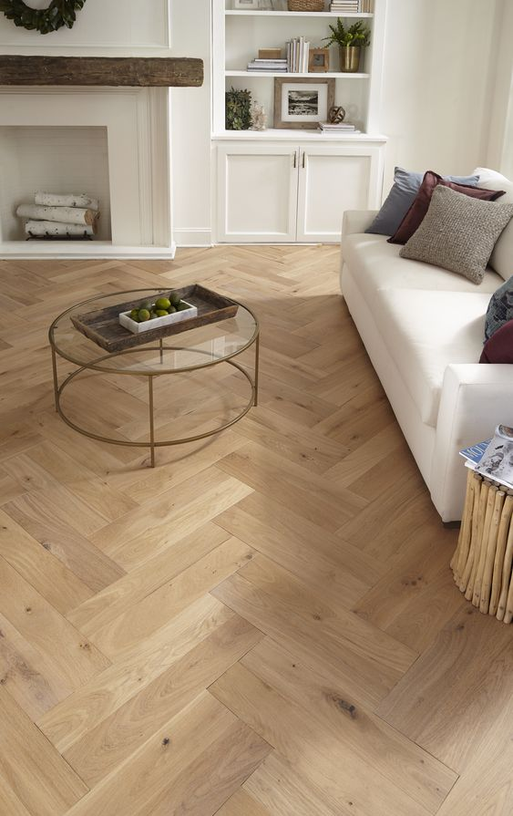 a chic living room with light stained hardwood herringbone floors, white built in and seating furniture, a non working fireplace