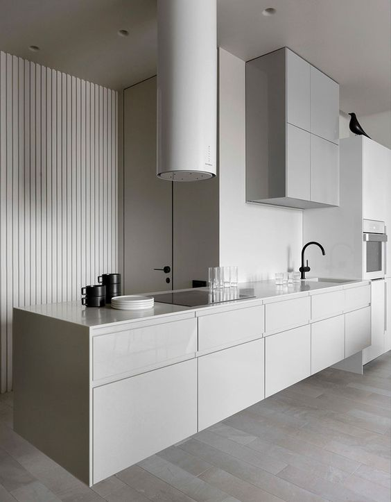 a chic minimalist kitchen in light grey with sleek cabinets, a round hood, black fixtures and other black touches for a contrast