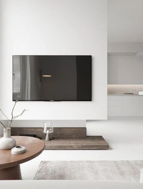 a chic minimalist living room in white with a touch of wood, a TV, a round table and neutral textiles is amazing