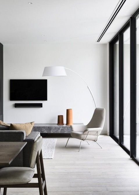 a chic minimalist space with a glazed wall, a stone TV unit, stylish furniture, a floor lamp and a dining space right here