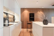 a chic minimalist white kitchen with sleek cabinets, stained ones with appliances, a mirror backsplash and shiny fixtures