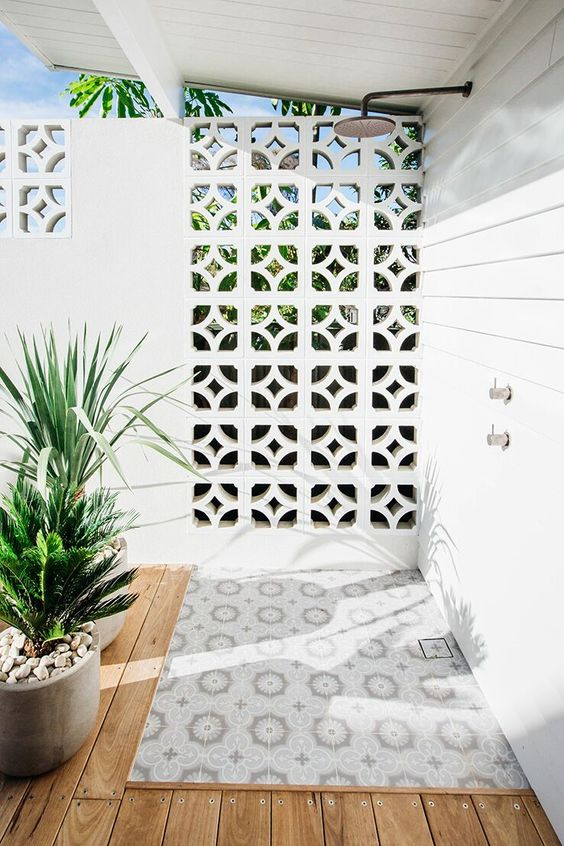 a chic modern outdoor shower with a laser cut wall, a wooden deck and a mosaic tile floor plus growing plants in pots