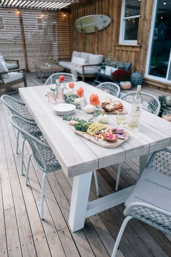 a chic outdoor dining space with a whitewashed dining table and grey wicker chairs plus white pumpkins and bold blooms