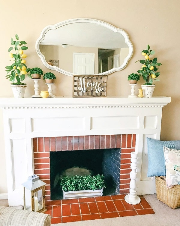 a classic farmhouse summer mantel with potted greenery, faux lemons, a mirror and a box with greenery in the fireplace
