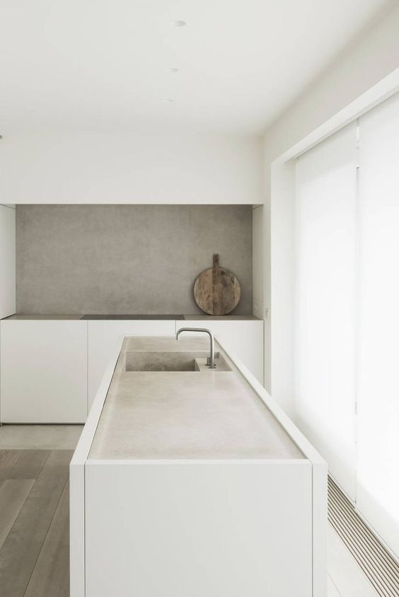 a clean minimalist kitchen in white, with sleek cabinets, a concrete backsplash and countertops plus a glazed wall for a view
