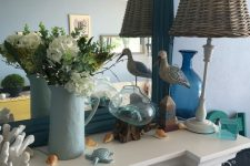 a coastal and farmhouse mantel with a sea gull, a faux turtle, a coral, some seashells, some blooms and a woven lamp