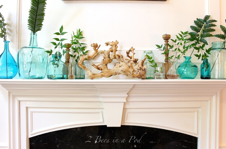 a coastal-inspired mantel with blue vases, jars and bottles and a single leaf in each of them, driftwood and candles is cool