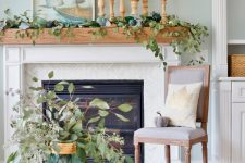 a coastal mantel covered with greenery, with blue pumpkins to embrace the fall, a coastal artwork and candles in wooden candleholders