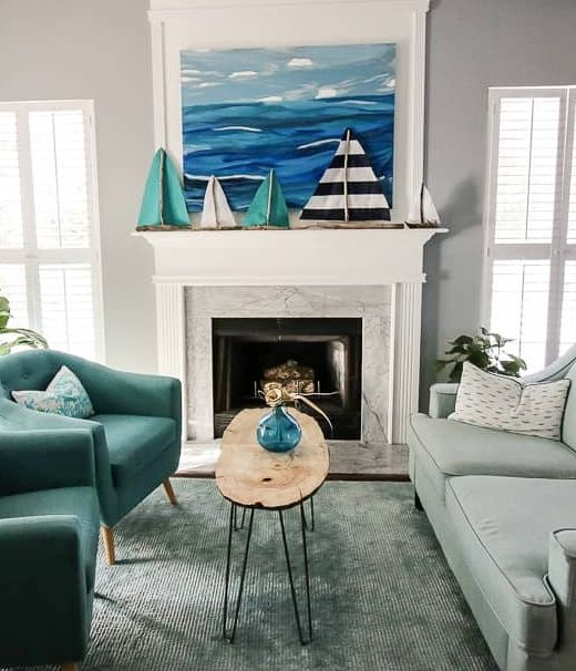 a coastal mantel with a bold sea artwork and several boats doubles as a stand for kids' artworks and crafts and looks cool