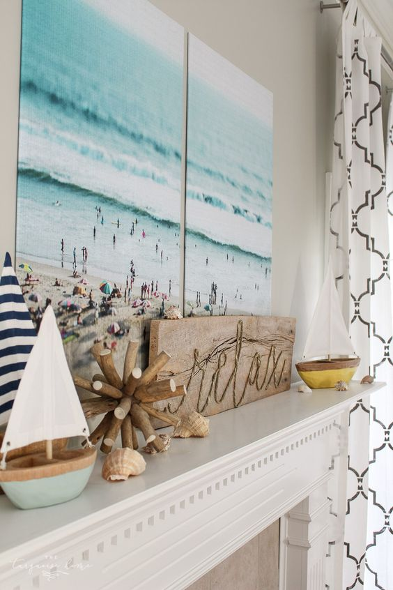 a coastal mantel with a vacation photo as a centerpiece, a wooden sign and wooden decor, a couple of boats and seashells