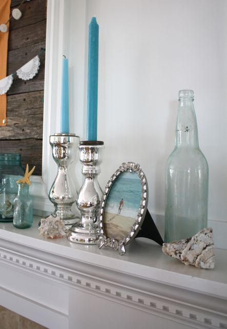 a coastal mantel with blue candles, bottles and jars, silver candleholders, a photo on the beach is personalized
