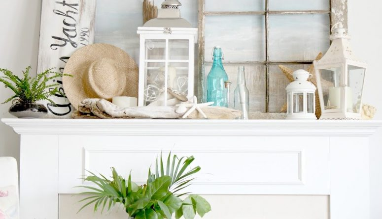 a coastal mantel with driftwood, starfish, candle lanterns, a straw hat, potted greenery and a vintage window frame