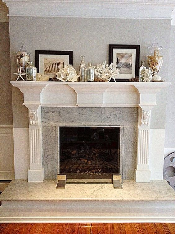 a coastal mantel with starfish and seashells, with black and white artworks and large jars with seashells feels very beachy