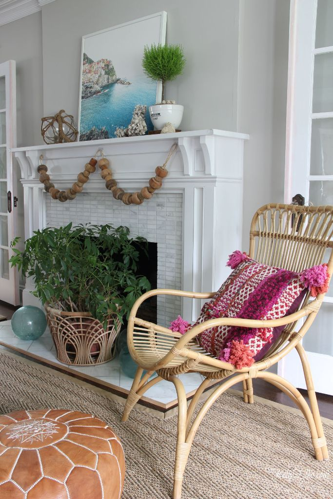 a coastal summer mantel with a gorgeous artwork, a wooden bead garland, buoys, potted plants and a rattan basket