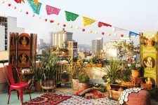 a colorful boho rooftop terrace with bright cushions, pillows and rugs, with bold furniture and lots of potted greenery plus colorful decor