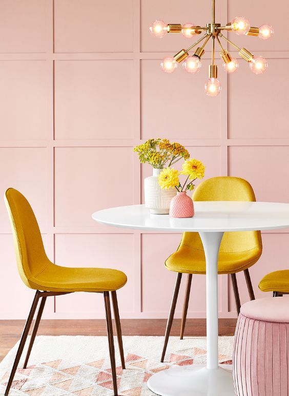 a colorful dining room with blush paneled walls, a round table, yellow chairs and a pink pouf plus a mid-century modern chandelier