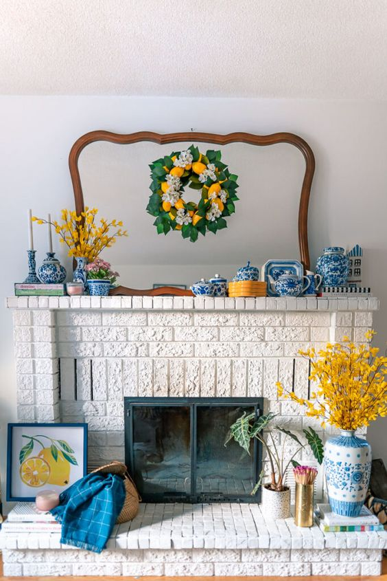 a colorful summer mantel with a lemon wreath, a yellow flower arrangement, chinoiserie, bright blue textiles and yellow branches