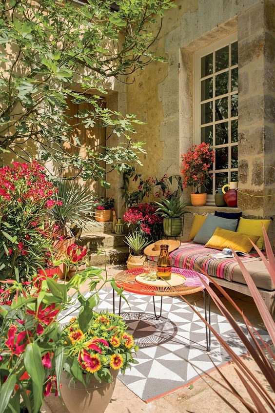 a colorful summer terrace with a daybed with colorful pillows, a woven coffee table, a printed rug, potted blooms and plants feels Mediterranean