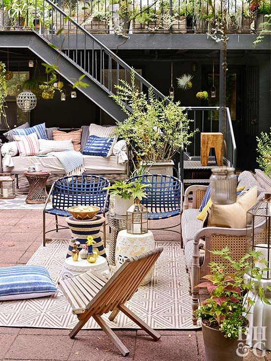 a colorful summer terrace with a tiled floor, rattan and wooden furniture, colorful printed pillows, blue accessories for a coastal feel
