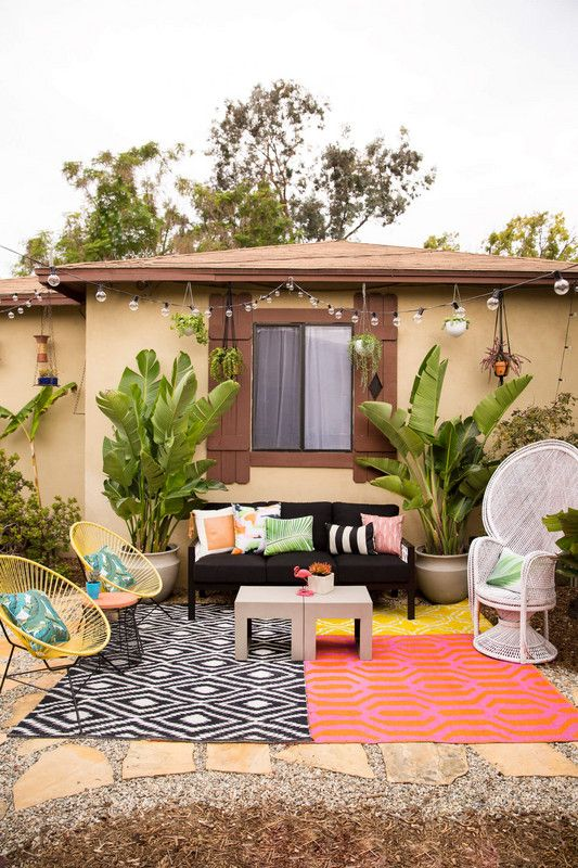 a colorful summer terrace with bright printed rugs, a black sofa, a peacock chair, yellow round chairs, printed pillows and potted tropical plants