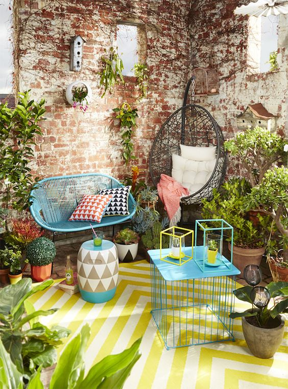 a colorful terrace with bold blue furniture, a printed yellow rug and a matching chevron side table, potted greenery and candle lanterns is fun