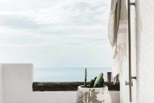 a contemporary Mediterranean shower space with a sea view, a wooden deck, a large shabby chic planter, a stool and a tree stump