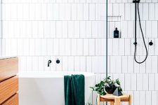 a contemporary bathroom with white skinny tiles and a bright terrazzo floor, a floating vanity and a wooden stool plus black fixtures