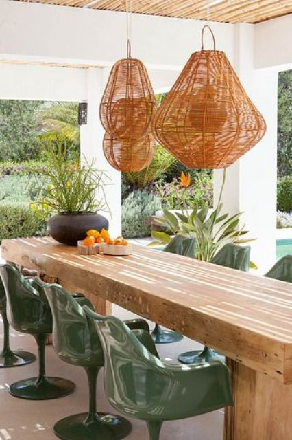 a contemporary dining space with a long table with a thick tabletop, woven pendant lamps, green chairs and potted plants is chic