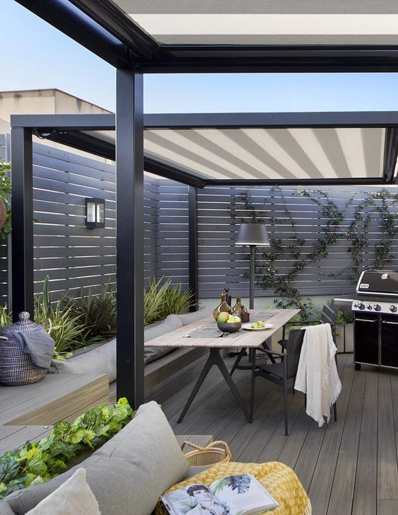 a contemporary outdoor dining space with a sleek built-in bench, a lightweight table and black chairs, a grill and a floor lamp by its side