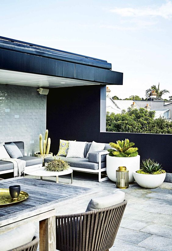 a scandinavian rooftop terrace clad with tiles, with elegant modern furniture and neutral pillows, potted plants and a dining space with wooden furniture