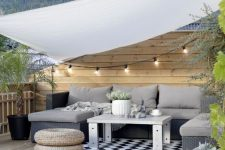 a contemporary rooftop terrace with a wooden deck, a grey sectional, jute poufs and potted plants plus lights over the space