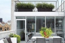 a contemporary rooftop terrace with a wooden deck, a large sofa, a dining set with metal chairs and potted greenery is cool and chic