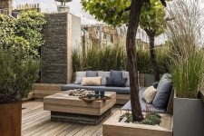 a contemporary rooftop terrace with growing grasses and potted trees, with a buit-in bench and a low coffee table is inviting