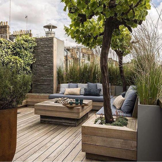 a contemporary rooftop terrace with growing grasses and potted trees, with a buit in bench and a low coffee table is inviting