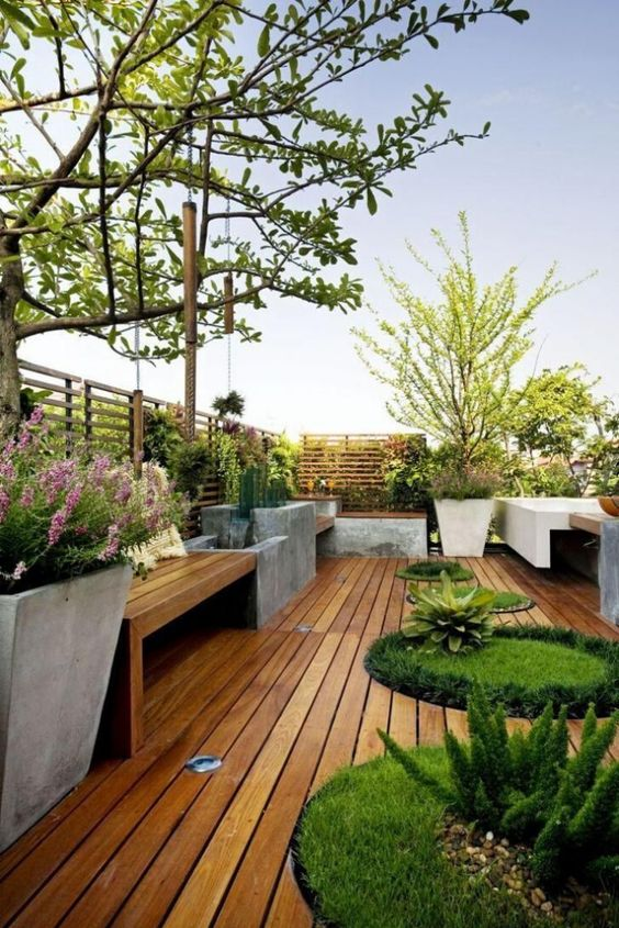 a contemporary rooftop terrace with potted plants and even trees, a wooden deck and concrete and wood furniture