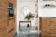 a contemporary space with white walls, a black and white terrazzo floor, chic stained cabinets and open shelves is a lovely room