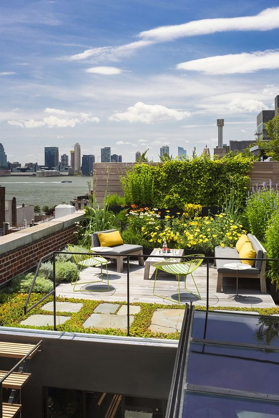 a cool and bright modern rooftop terrace with greenery and bright yellow blooms, stylish and simple furniture, bright pillows and bold neon chairs