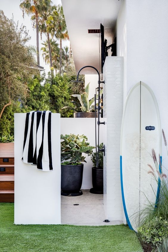 a cool and private outdoor shower with a tiled floor and potted plants plus towel on the wall is a lovely space
