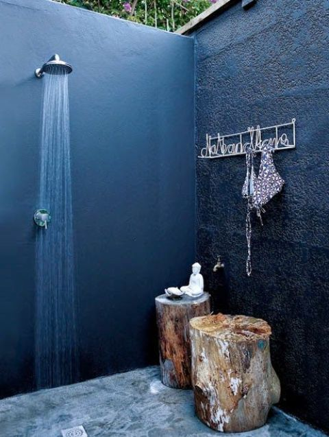 a cool and private outdoor shower with black walls, a concrete floor, tree stump stools and a holder is a lovely idea