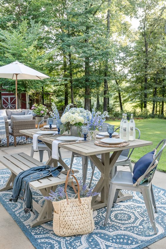 a cool coastal outdoor dining space with a trestle table and a bench, metal chairs, blue textiles, blooms and glasses is amazing