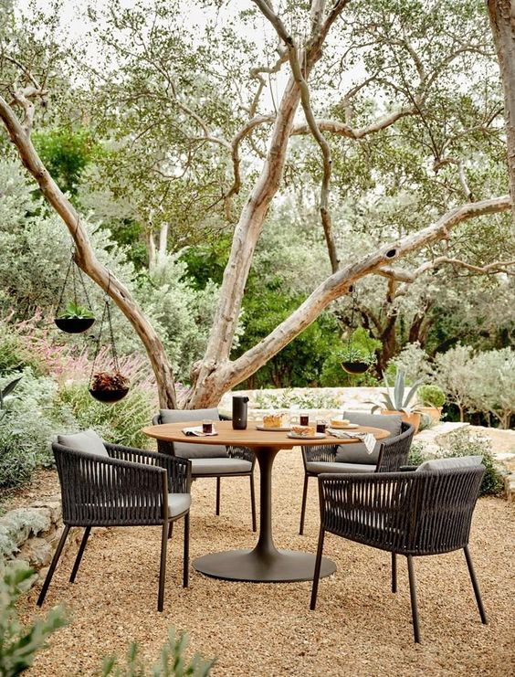 a cool contemporary dining space located by a tree with pendant planters, with a round table and black rattan chairs is cool