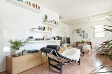 a cool living room with white walls and a pink terrazzo floor, open shelves, a lounger and a wooden storage unit