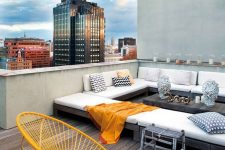a cool modern rooftop terrace with a wooden deck, a large sectional, some cool chairs and printed pillows is welcoming