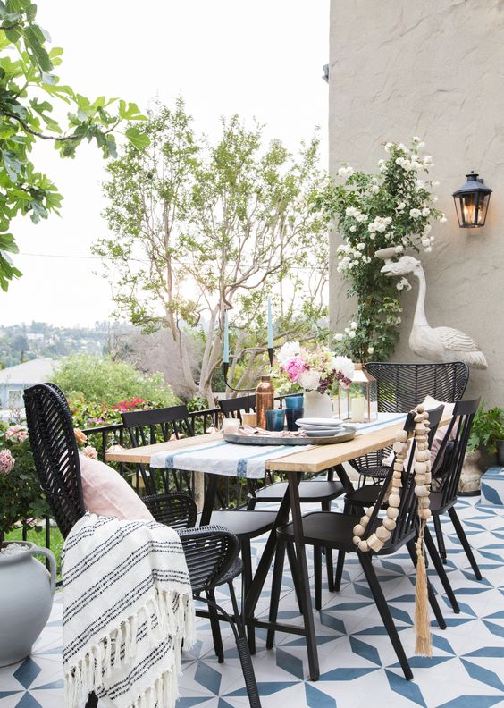 a cool outdoor dining space with a lightweight table, black wooden and rattan chairs, blankets and beads, potted greenery and blooms
