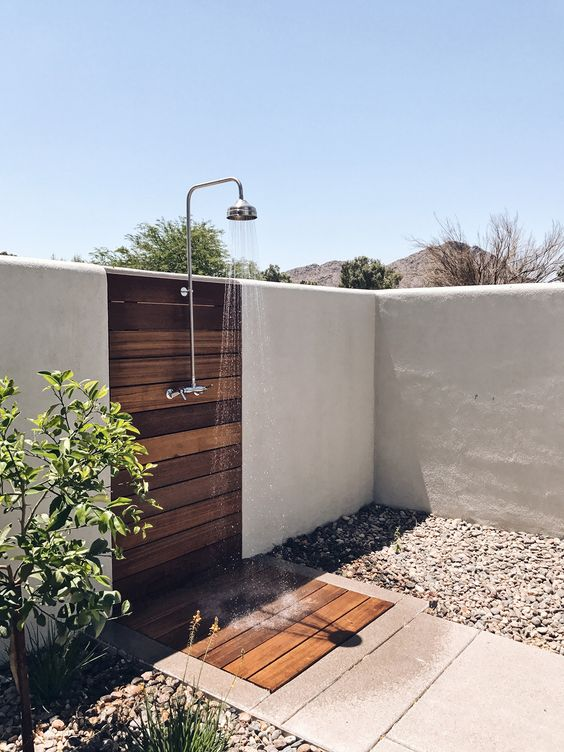 a cool private outdoor shower with a wooden deck and tiles, with pebbles around and some plants growing is amazing