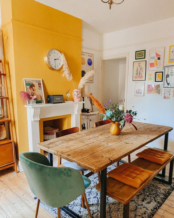 a cozy eclectic dining room with a yellow accent wall and a yellow fireplace, a wooden table, mismatching chairs and benches and a bold gallery wall