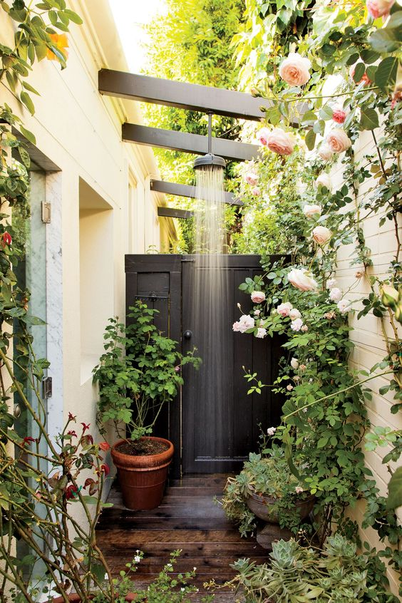 a cozy little shower space with a black wall, a wooden deck and lots of greenery and blooms growing around is amazing