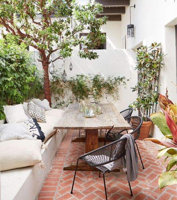 a cozy outdoor dining space with a built-in bench and lots of pillows, a rough wooden table, black rattan chairs and potted plants