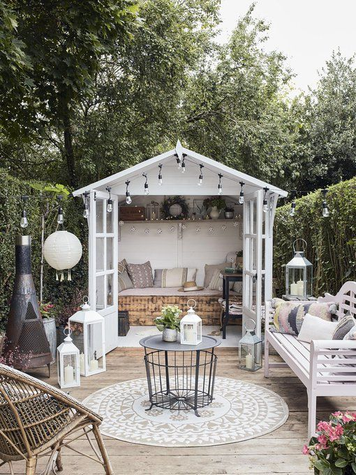 a cozy small terrace with a hearth, a white bench with lots of pillows, a coffee table, a rattan chait, lots of lanterns and a small shed with a daybed