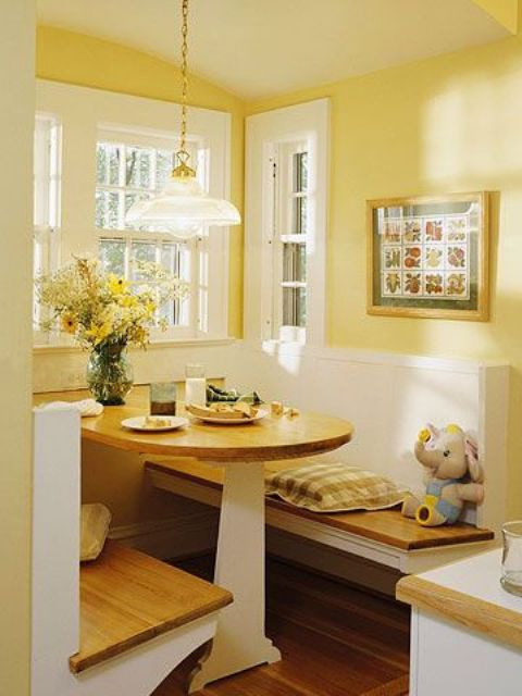 a cozy yellow dining space with yellow walls and white paneling, a folding table and built-in benches, a pendant lamp and a bold artwork